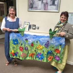 Two adies holding an art painted fabric